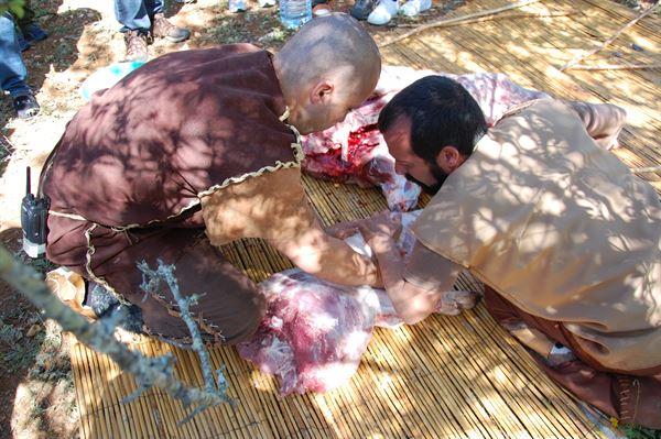 Pedro Cura e Nuno Silva a cortarem a carne com as lâminas de sílex