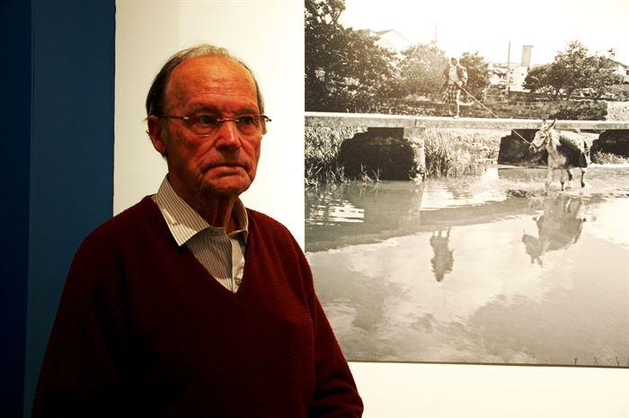 O barbeiro fotógrafo António Marreiros junto a uma das suas fotos na exposição