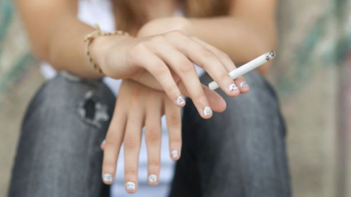 Teenage hands holding cigarette