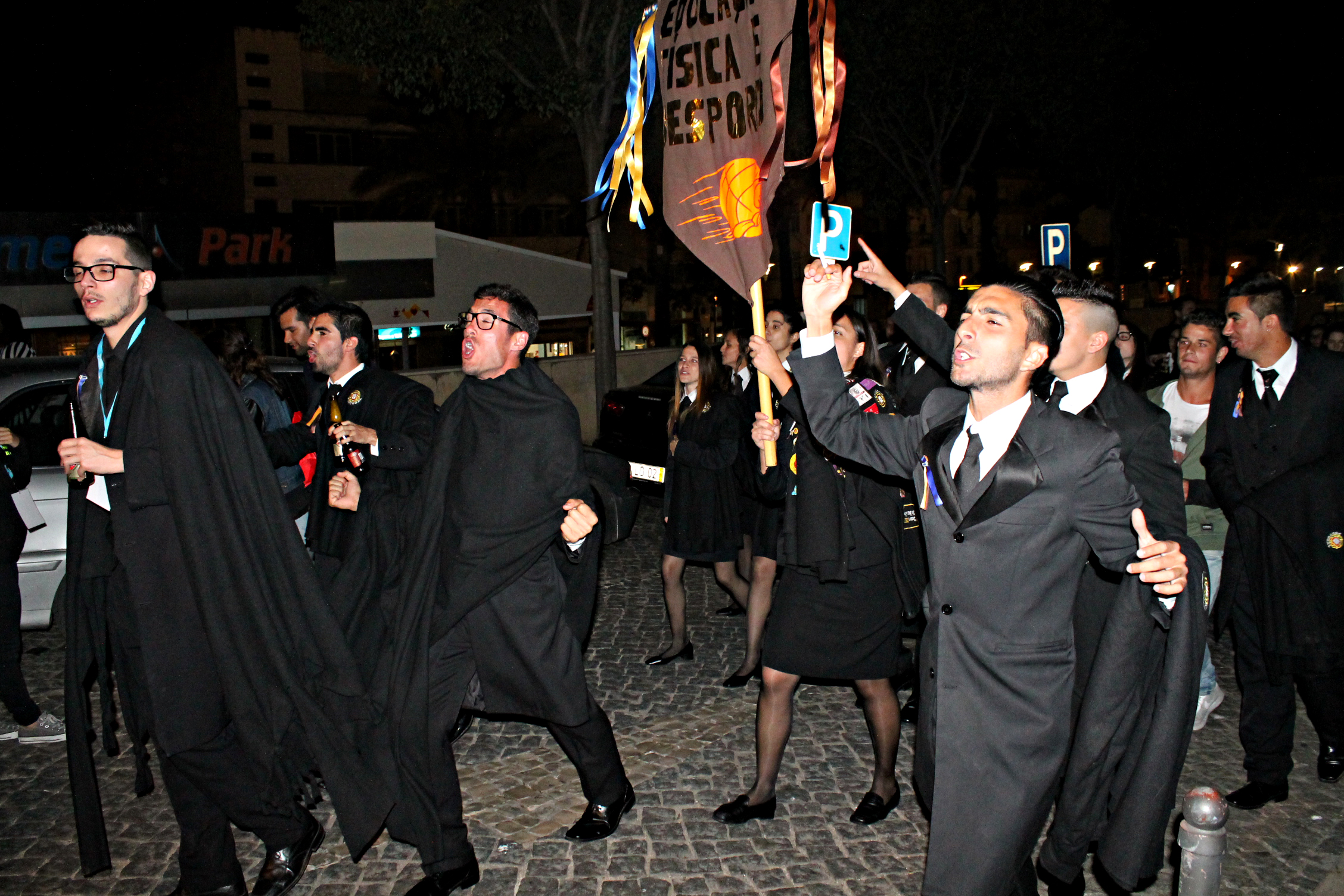 Estudantes com traje académico à noite