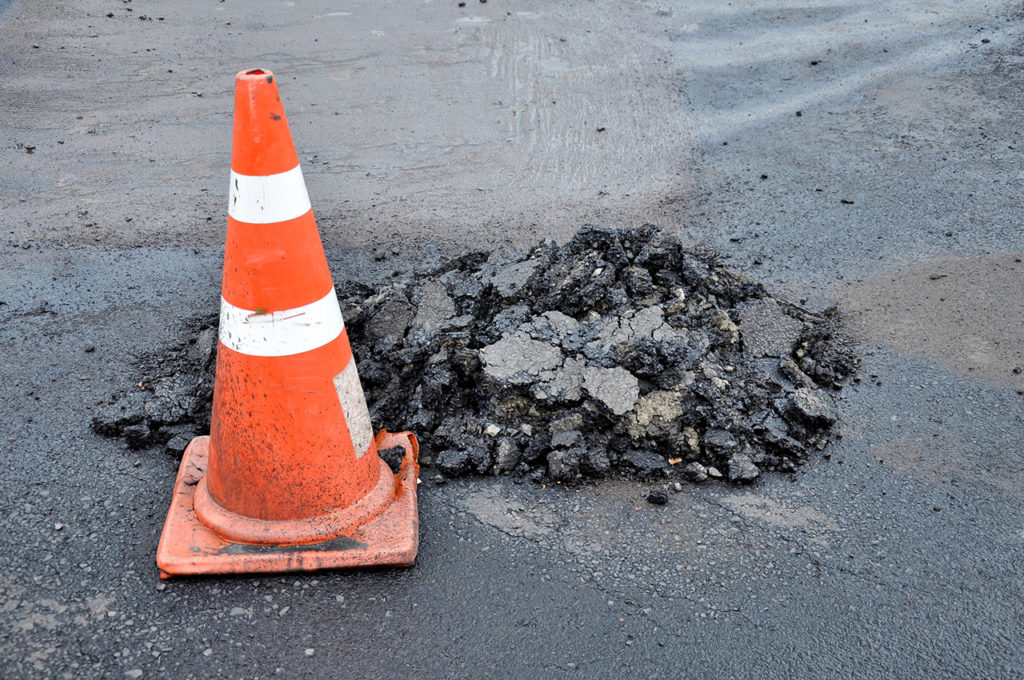 Traffic cones and mounds of asphalt
