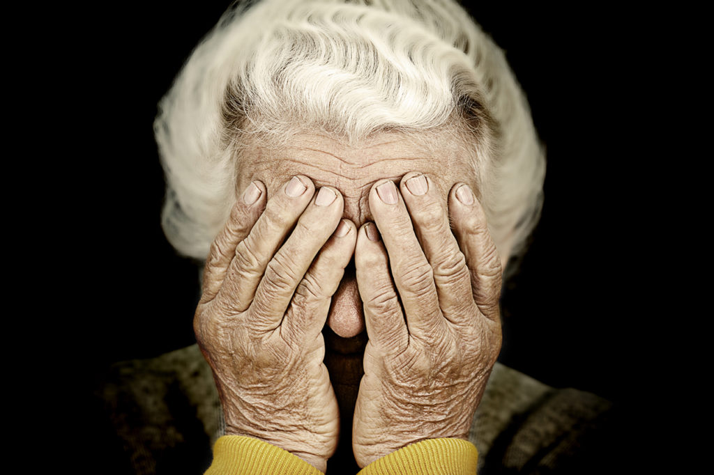 Closeup portrait depressed old woman covering her face with hand